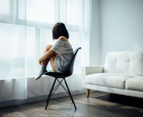 A woman sits on a chair and looks out a window